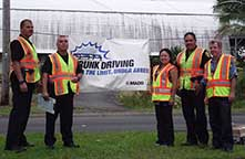 Image: officers and civilians standing by an anti-drunk driving sign.