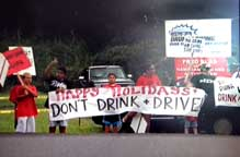 Image: community members wave signs advising motorists not to drink and drive.