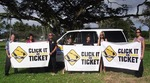 Image of sign wavers holding three large 'Click It or Ticket' signs