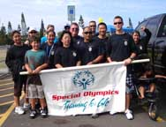 "A group of participants stand with a banner reading ""Special Olympics Training for Life"""