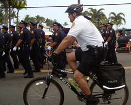 office on bicycle next to marching officers