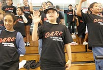 students wearing DARE t-shirts raise their right hands
