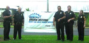 "Image: 5 officers pose next to a ""drunk driving"" sign"