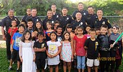 Image: large group of officers and kids.