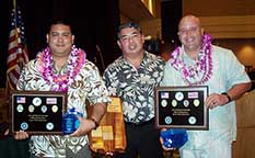 Image: Honored officers wearing leis and holding plaques pose with the deputy chief.