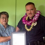 Aloha Exchange President Dale Tokuuke presents an 'Officer of the Month' award to Officer Michael Santos