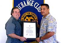 Photo: Officer Correa, holding a framed certificate stands between Chruchill and Estrell in front of the Exchange Club banner